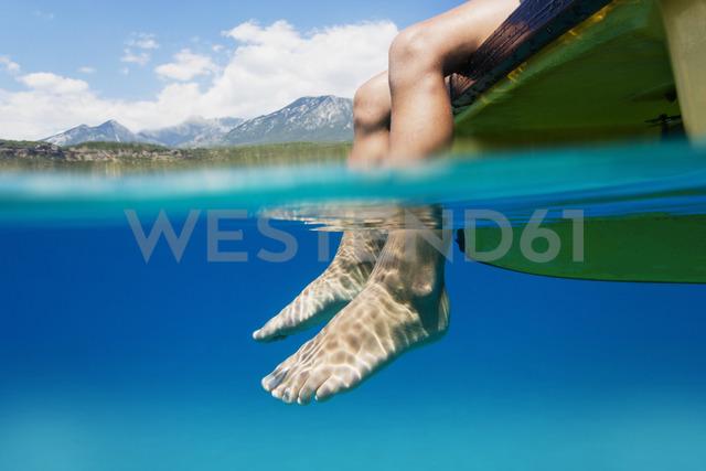 Feet of a boy sitting on boat dangling in water - AZOF00041