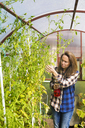 Gardener Woman Watering Plant With Spray Bottle - AURF05025