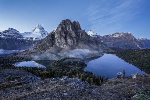Man overlooks a lake at dawn, Mount Assinboine Provincial Park, British Columbia, Canada - AURF05319