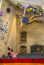 Mother And Daughter Looking At Man Climbing Wall At Indoor Gym In House - AURF05325