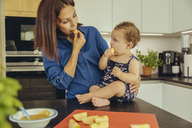 Mother and baby daughter eating apple chunks in kitchen together - MFF04648