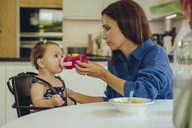 Mother helping baby daughter drinking water from bottle in kitchen - MFF04654
