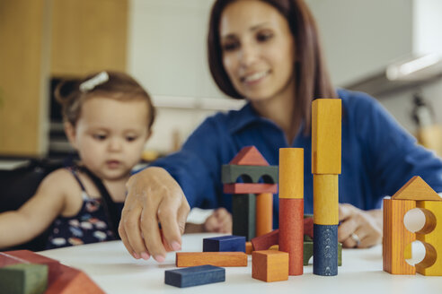 Happy mother and baby daughter playing with building blocks - MFF04657