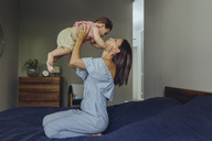 Mother lifting up her baby girl on bed - MFF04660