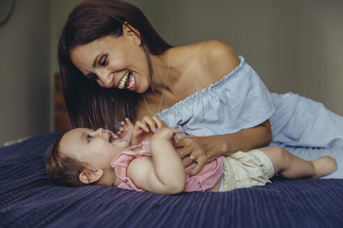 Happy mother playing with her baby girl on bed - MFF04663