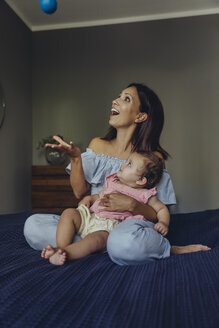 Happy mother playing with her baby girl on bed - MFF04666