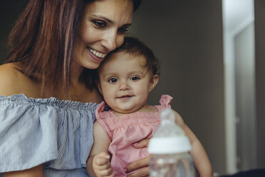Mother offering her baby girl milk in a bottle - MFF04669