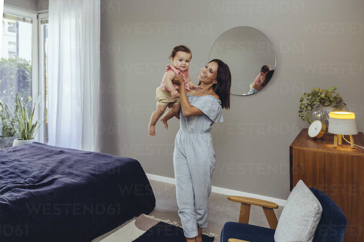 Happy mother carrying her baby girl at home - MFF04672 - Mareen Fischinger/Westend61
