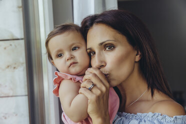 Mother looking out of window with baby daughter at home - MFF04675