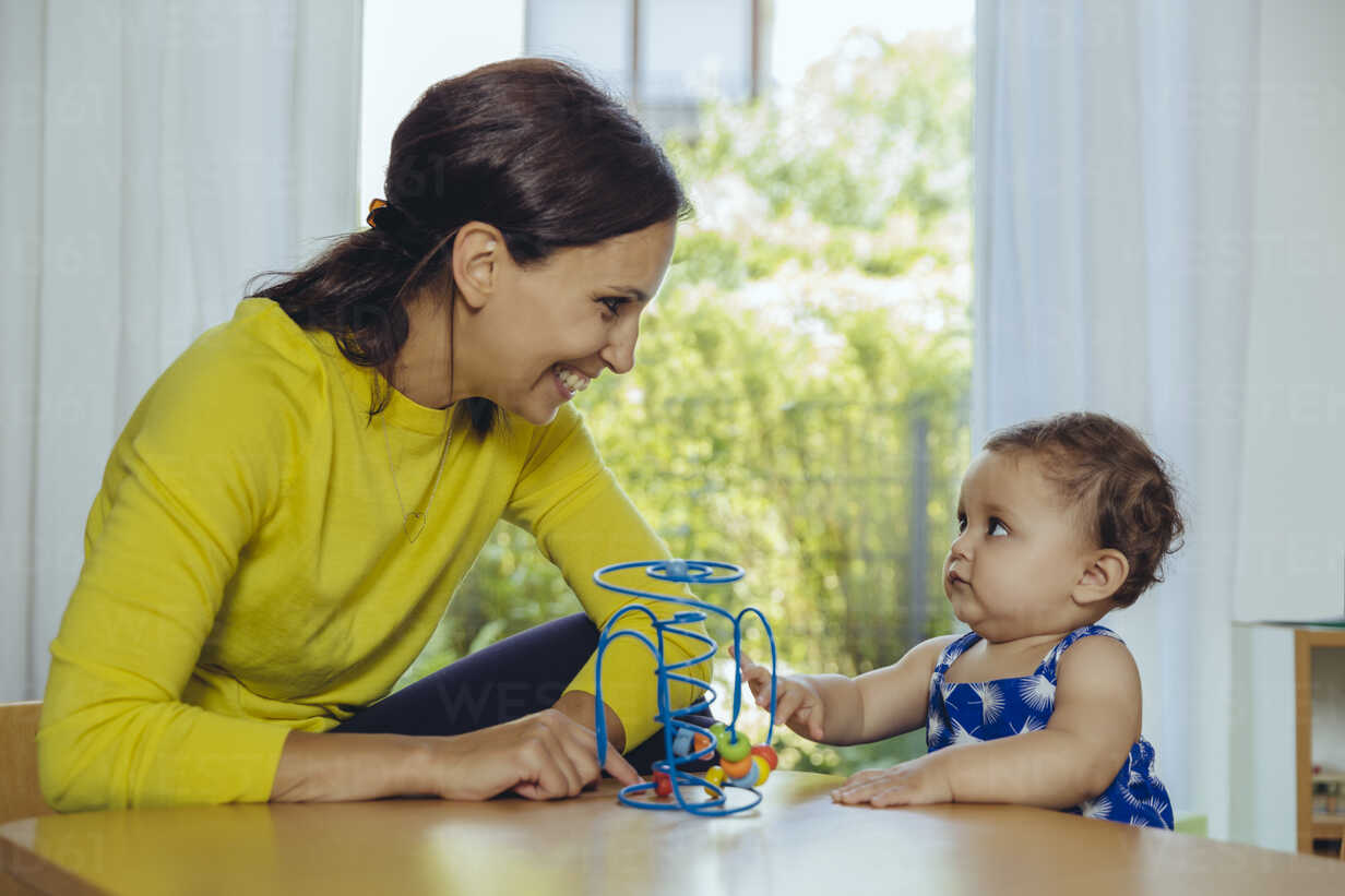 Happy mother and baby daughter playing with motoric loop - MFF04678 - Mareen Fischinger/Westend61