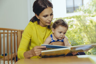 Mother and baby daughter looking at children's book - MFF04681
