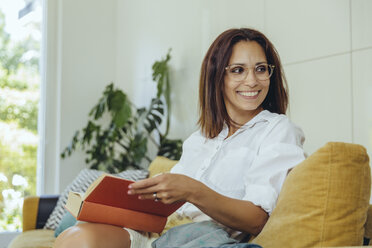 Smiling woman looking up from reading book on couch - MFF04699