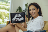 Portrait of smiling woman showing ultrasound picture of unborn child on couch - MFF04705