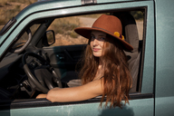 Portrait of smiling young woman wearing a hat sitting in a car - AFVF01559