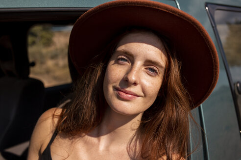 Portrait of smiling young woman wearing a hat in a car - AFVF01562
