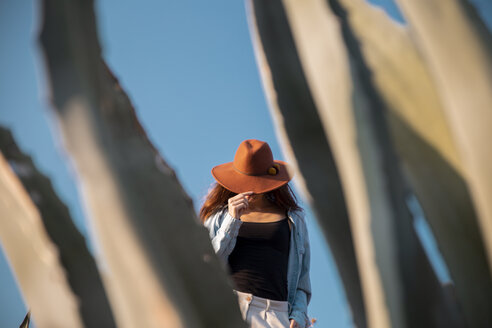 Young woman wearing a hat behind an agave in the countyside - AFVF01571