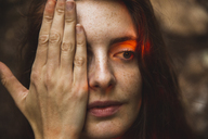 Portrait of young woman with freckles covering one eye - AFVF01577