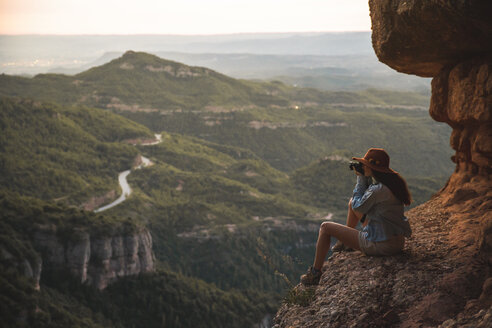 Young woman on a hiking trip wearing a hat sitting on a rock taking a picture - AFVF01586