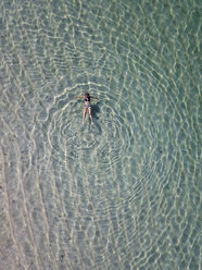 Indonesia, Bali, Aerial view of Karma Kandara beach, one woman floating in water - KNTF01656