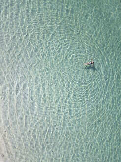 Indonesia, Bali, Melasti, Aerial view of Karma Kandara beach, woman in water - KNTF01659