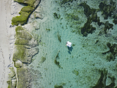 Indonesia, Bali, Aerial view of Karma Kandara beach, one woman, airbed floating on water - KNTF01668
