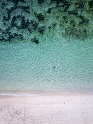 Indonesia, Bali, Melasti, Aerial view of Karma Kandara beach, woman swimming - KNTF01680