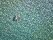 Indonesia, Bali, Melasti, Aerial view of Karma Kandara beach, woman floating on water - KNTF01683