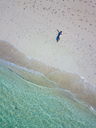 Indonesia, Bali, Melasti, Aerial view of Karma Kandara beach, woman lying on beach - KNTF01692