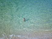 Indonesia, Bali, Melasti, Aerial view of Karma Kandara beach, woman going into water - KNTF01695