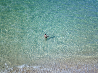 Indonesia, Bali, Melasti, Aerial view of Karma Kandara beach, woman going into water - KNTF01695