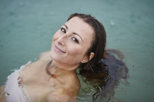 Portrait of smiling young woman  bathing in lake on rainy day - PNEF00884