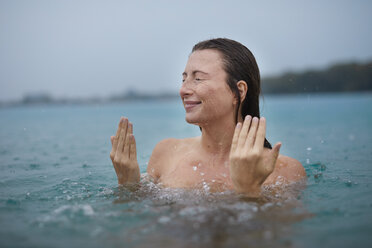 Portrait of young woman bathing in lake on rainy day - PNEF00893