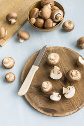 Sliced and whole Crimini Mushrooms on wooden board - JUNF01271