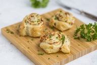 Sticky buns with feta, cream cheese, bacon and parsley on wooden board - JUNF01277