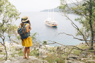 Croatia, Cres, woman standing at the coast looking at the sea with sailing ship - JES00154