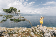 Croatia, Cres, woman standing at the coast looking at the sea - JES00157
