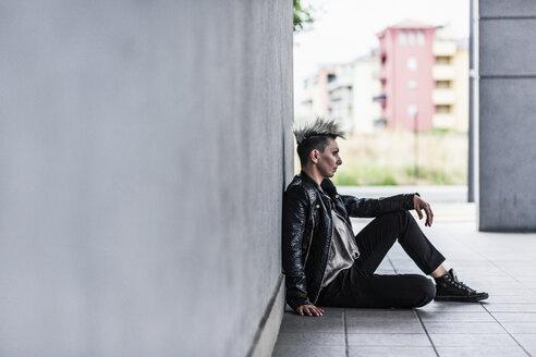 Punk woman sitting at a wall - GIOF04423