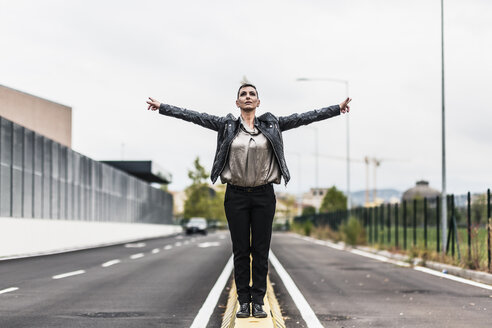Punk woman standing on a barrier at the roadside with outstretched arms - GIOF04426