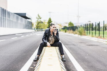 Punk woman sitting at the roadside using cell phone - GIOF04435