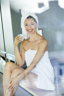 Portrait of smiling woman wrapped in towels drinking cup of coffee in the kitchen - PNEF00914