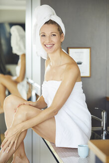 Portrait of smiling woman wrapped in towels sitting on sink in the kitchen - PNEF00917