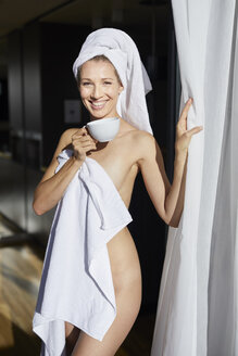 Portrait of laughing woman wrapped in towel standing with cup of coffee at open balcony door - PNEF00923