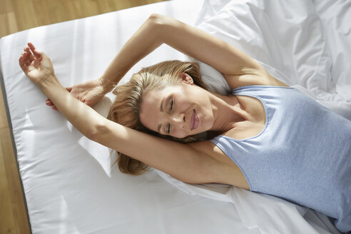Portrait of blond woman lying in bed in the morning - PNEF00926