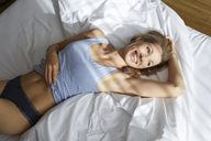 Portrait of blond woman relaxing on bed in the morning - PNEF00929