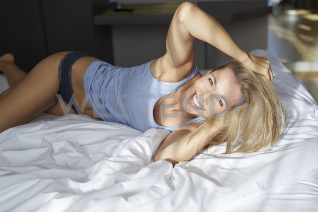 Portrait of laughing blond woman lying in bed in the morning - PNEF00932 - Philipp Nemenz/Westend61