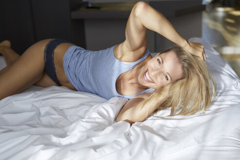 Portrait of laughing blond woman lying in bed in the morning - PNEF00932