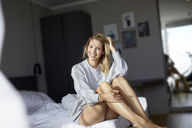 Portrait of smiling blond woman sitting on bed in the morning - PNEF00935