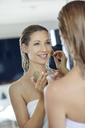 Mirror image of smiling blond woman applying makeup - PNEF00941