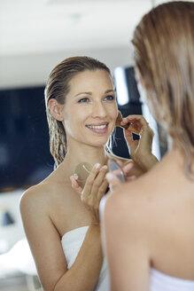 Mirror image of smiling blond woman applying makeup - PNEF00941