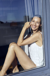 Portrait of smiling woman wrapped in towel sitting behind glass door - PNEF00944